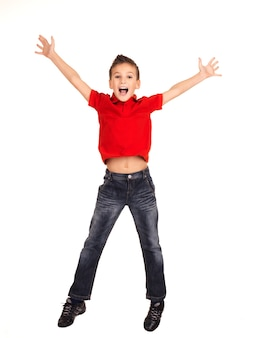 Portret van lachende gelukkige jongen springen met opgeheven handen omhoog -