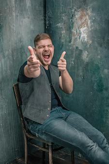 Portret van lachende gelukkige man zittend op de stoel, duimen omhoog