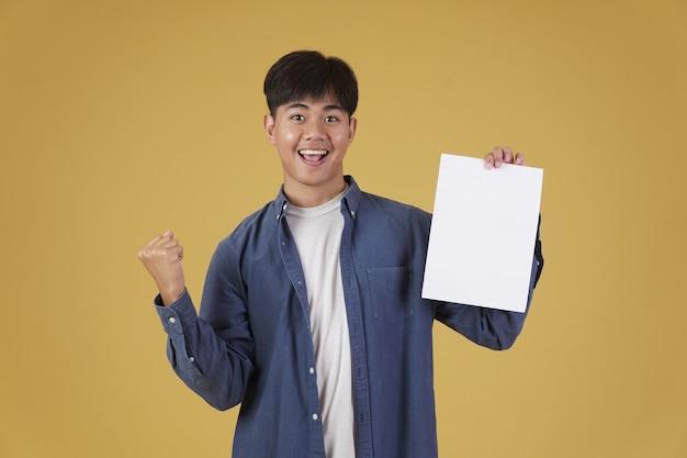 Portret van lachende gelukkige vrolijke jonge aziatische man terloops gekleed tonen blanco leeg aanplakbiljet papier geïsoleerd.