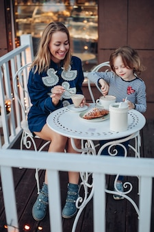 Portret van lachende gelukkige vrouw met blond haar in blauwe jurk met eenden en blauwe laarzen genietend van kopje koffie met haar dochter in café. mooi meisje roeren cacao zittend door moeder aan tafel buiten.