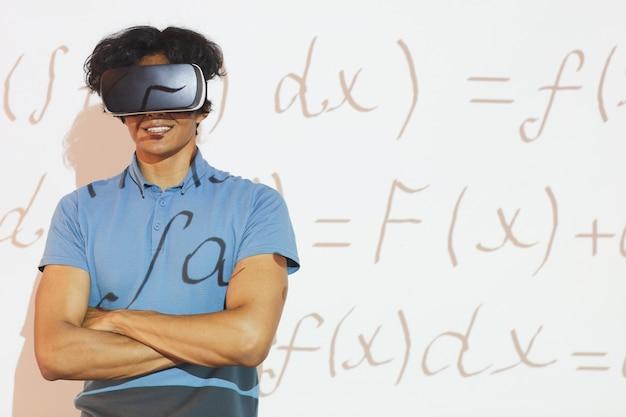 Portret van lachende gemengd ras student jongen in virtual reality headset staande met gekruiste armen tegen projectiescherm met wiskundige formule