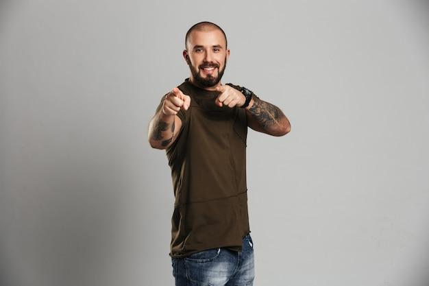 Portret van lachende gespierde man met tatoeage op zijn armen wijzende vingers, geïsoleerd over grijze muur