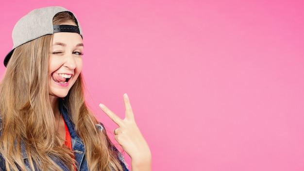 Portret van lachende hippster brunette in cap bedrijf vingers.