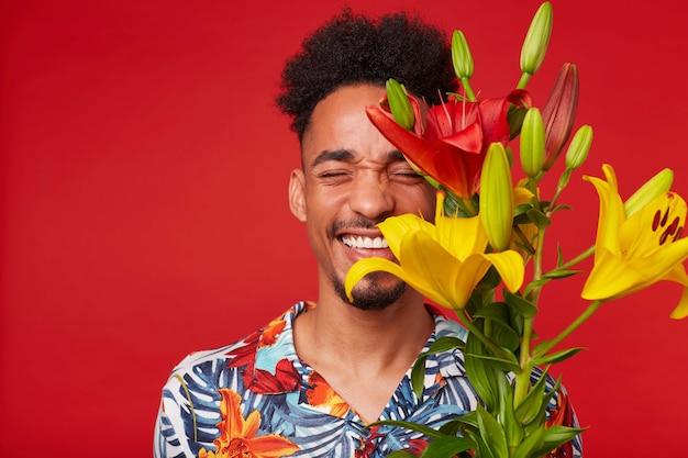 Portret van lachende jonge afro-amerikaanse man, draagt in hawaiiaans shirt, kijkt naar de camera met gelukkige uitdrukking, houdt gele en rode bloemen, staat op rode achtergrond met gesloten ogen.