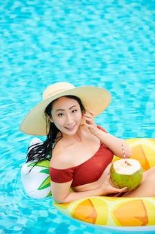 Portret van lachende jonge aziatische vrouw in zomerhoed zittend in opblaasbare ring in de vorm van ananas...