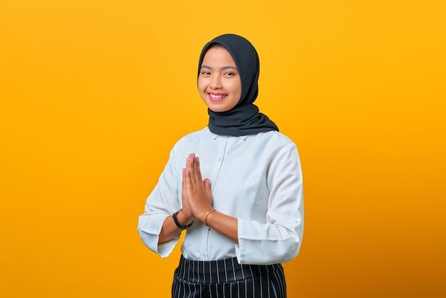 Portret van lachende jonge aziatische vrouw welkome uitdrukking op gele achtergrond
