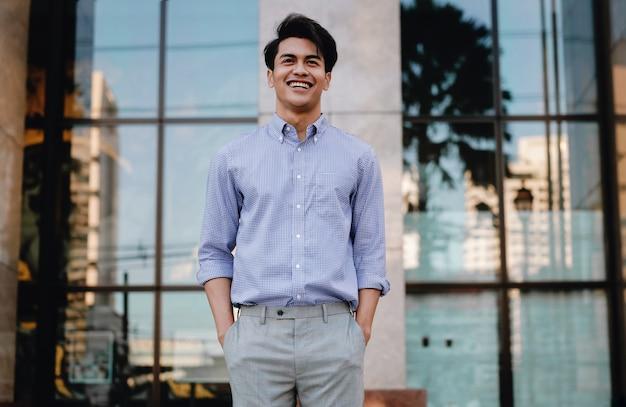 Portret van lachende jonge aziatische zakenman in de stad. een gelukkig vriendelijke man