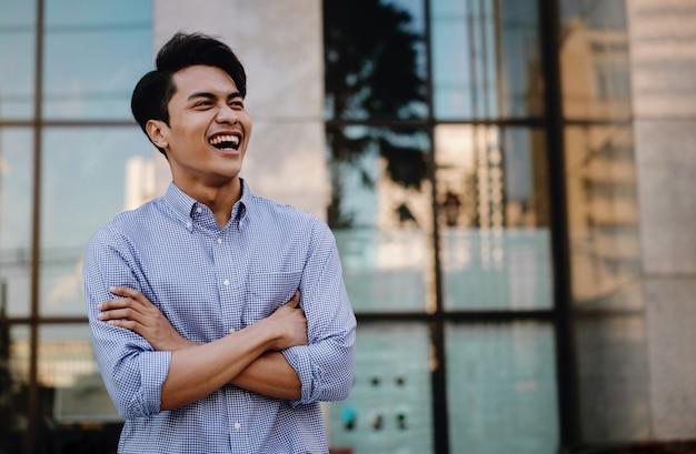 Portret van lachende jonge aziatische zakenman in de stad. gekruiste armen en wegkijken. een gelukkig vriendelijke man