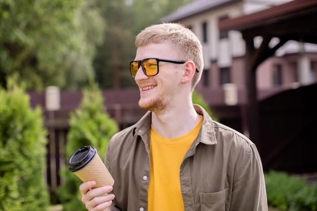 Portret van lachende jonge bebaarde man in gele glazen terloops gekleed wegwerp kartonnen beker buiten houden op zonnige zomerdag