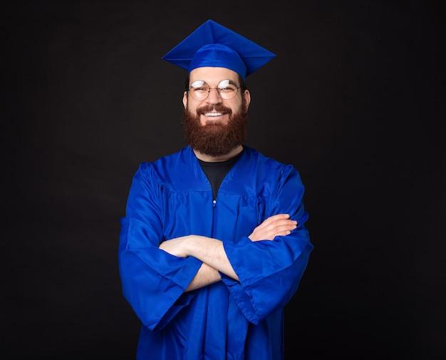 Portret van lachende jonge bebaarde man met blauwe mantel bachelor en permanent met gekruiste armen