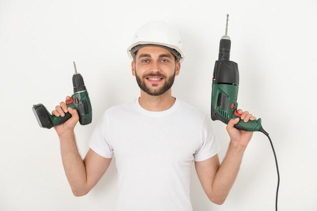 Portret van lachende jonge bebaarde reparateur in bouwvakker met draadloze schroevendraaier en boor tegen witte muur