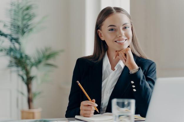 Portret van lachende jonge blanke zakenvrouw in zwart formeel pak zittend door groot wit bureau met notitieboek en laptop met licht wazig minimalistische achtergrond. mensen die van hun werk genieten