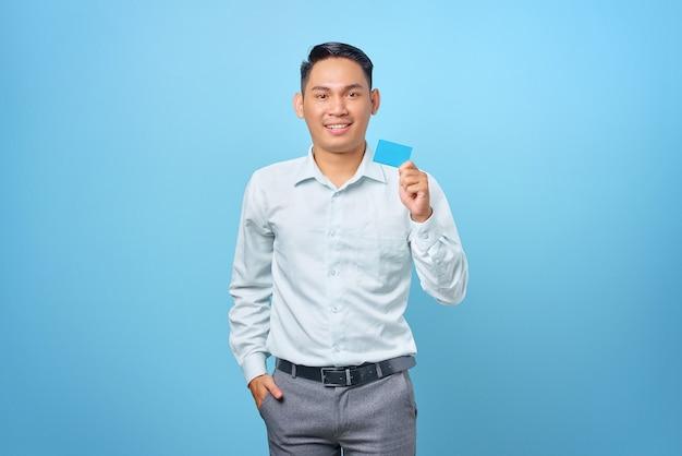 Portret van lachende jonge knappe zakenman die een creditcard in de hand houdt op blauwe achtergrond