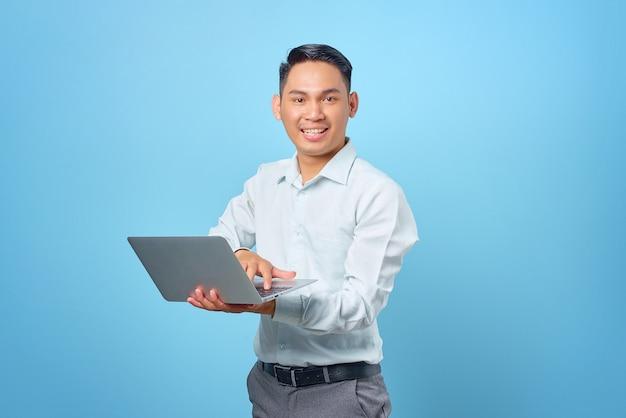 Portret van lachende jonge knappe zakenman die een laptop vasthoudt en gebruikt op blauwe achtergrond