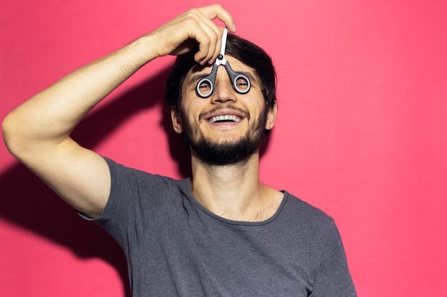 Portret van lachende jonge man met een schaar op de ogen in plaats van een bril. geïsoleerd op roze koraal oppervlak