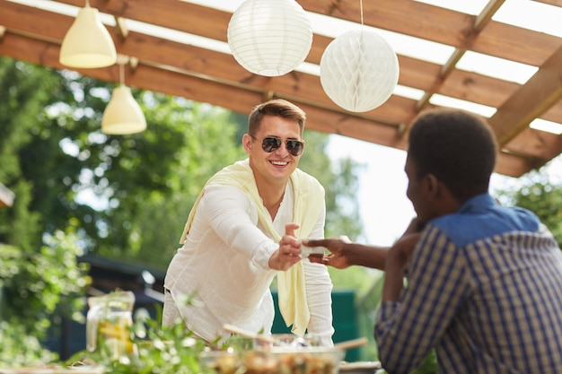 Portret van lachende jonge man met zonnebril saus doorgeven aan vriend over tafel terwijl u geniet van een diner in de buitenlucht op zomerfeest