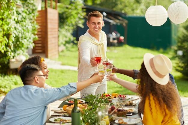Portret van lachende jonge man roosteren met vrienden terwijl u geniet van diner op terras in de zomer