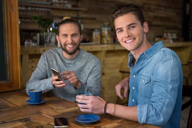 Portret van lachende jonge mannen zitten aan tafel in de coffeeshop