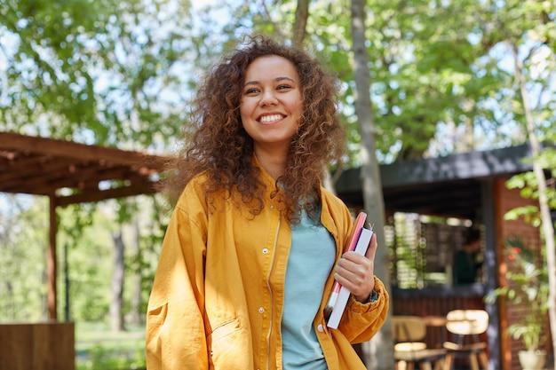 Portret van lachende jonge mooie donkere gekrulde student meisje op een café-terras, met schoolboeken, gekleed in gele jas, geniet van het weer.