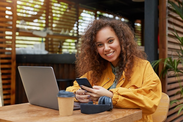 Portret van lachende jonge mooie donkere krullend student meisje op het terras van een café, met smartphone op zijn handen, gekleed in gele jas, geniet van de dag.