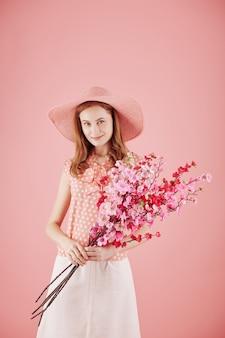 Portret van lachende jonge mooie vrouw in strooien hoed met takken van bloeiende oosterse kersen