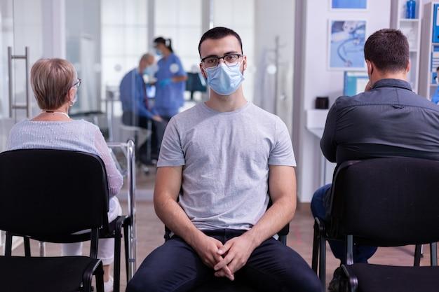 Portret van lachende jonge patiënt kijkend op camera zittend op een stoel in de wachtkamer van de ziekenhuiskliniek met respect voor sociale afstand terwijl de arts op de achtergrond werkt