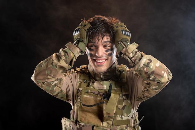 Portret van lachende jonge soldaat in camouflage-uniform
