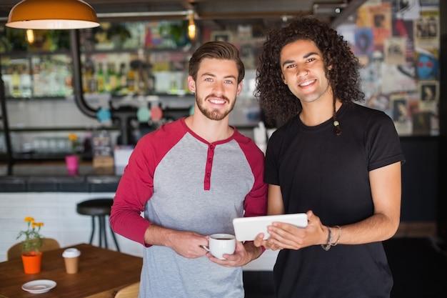 Portret van lachende jonge vrienden met behulp van digitale tablet in restaurant