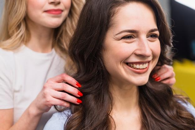 Portret van lachende jonge vrouw bij herenkapper