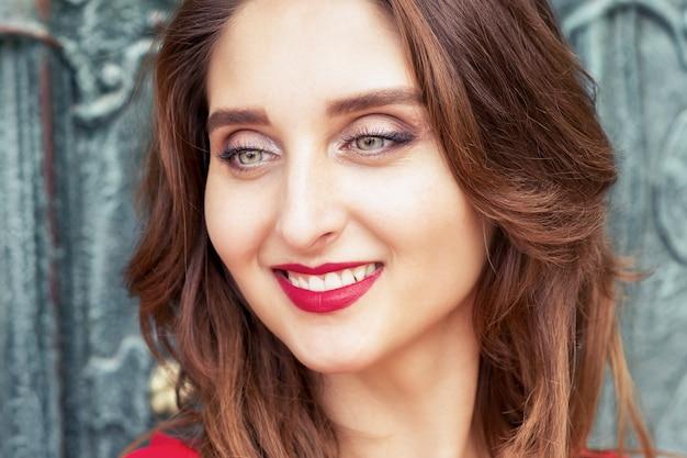 Portret van lachende jonge vrouw buitenshuis close-up.