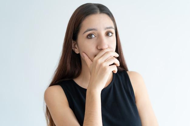 Portret van lachende jonge vrouw die mond behandelt met hand