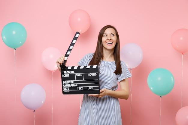 Portret van lachende jonge vrouw in blauwe jurk die omhoog kijkt met klassieke zwarte film die filmklapper maakt op roze achtergrond met kleurrijke luchtballonnen. verjaardagsfeestje, oprechte emoties van mensen.