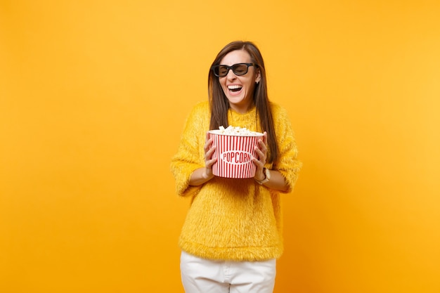 Portret van lachende jonge vrouw in bont trui 3d imax bril kijken naar film film met emmer popcorn geïsoleerd op felgele achtergrond. mensen oprechte emoties in bioscoop lifestyle concept.