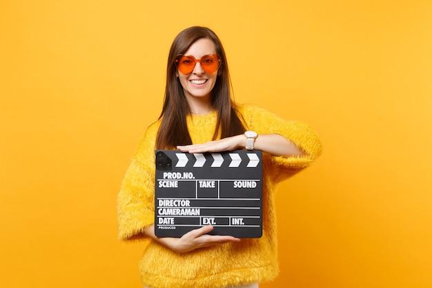 Portret van lachende jonge vrouw in bont trui, oranje hart brillen houden klassieke zwarte film filmklapper geïsoleerd op gele achtergrond. mensen oprechte emoties, levensstijl. reclame gebied.