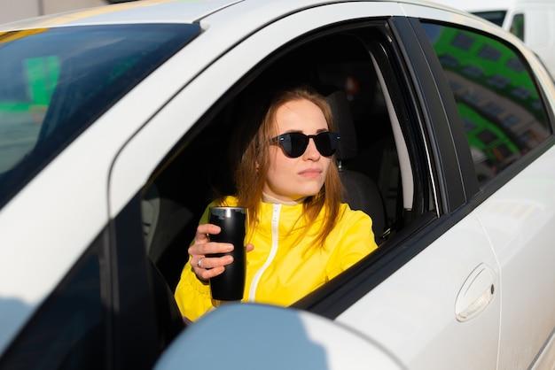 Portret van lachende jonge vrouw in een gele jas met een koffiepauze in haar auto.