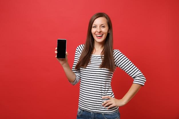 Portret van lachende jonge vrouw in gestreepte kleding met mobiele telefoon met leeg zwart leeg scherm geïsoleerd op heldere rode achtergrond. mensen oprechte emoties, lifestyle concept. bespotten kopie ruimte.