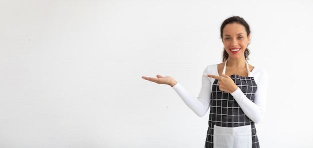 Portret van lachende jonge vrouw in schort kijken naar camera geïsoleerd op een witte achtergrond