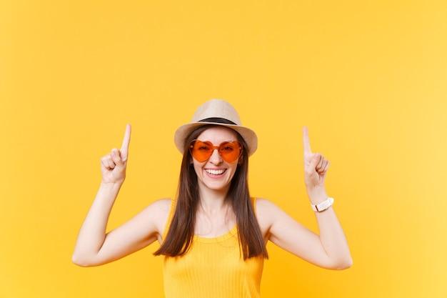 Portret van lachende jonge vrouw in stro zomer hoed, oranje bril wijzende wijsvingers omhoog op kopie ruimte geïsoleerd op gele achtergrond. mensen oprechte emoties, lifestyle concept. reclame gebied.