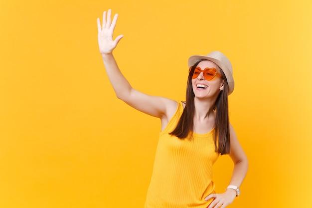 Portret van lachende jonge vrouw in stro zomer hoed, oranje bril zwaaien en groet hand als iemand merkt, kopieer ruimte geïsoleerd op gele achtergrond. mensen levensstijl concept. reclame gebied.