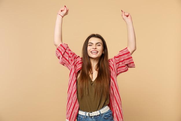 Portret van lachende jonge vrouw in vrijetijdskleding die handen opstijgt, vuisten balde als winnaar geïsoleerd op pastelbeige muurachtergrond. mensen oprechte emoties, lifestyle concept. bespotten kopie ruimte.
