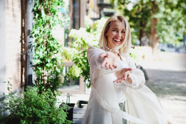 Portret van lachende jonge vrouw in witte trenchcoat die plezier heeft op straat dansende gelukkige blonde meid