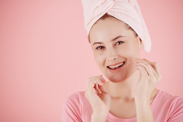 Portret van lachende jonge vrouw met behulp van tandzijde na het nemen van een douche