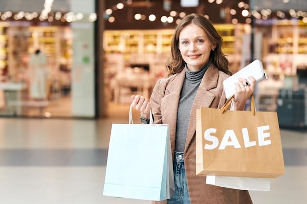Portret van lachende jonge vrouw met boodschappentassen en portemonnee genieten van seizoensgebonden verkoop in winkelcentrum