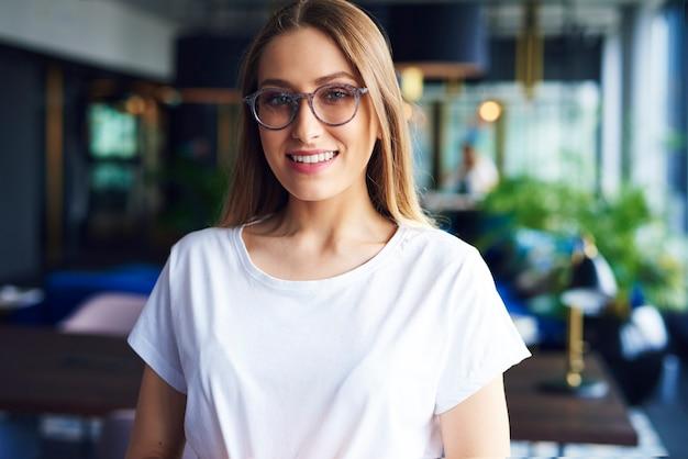 Portret van lachende, jonge vrouw met bril