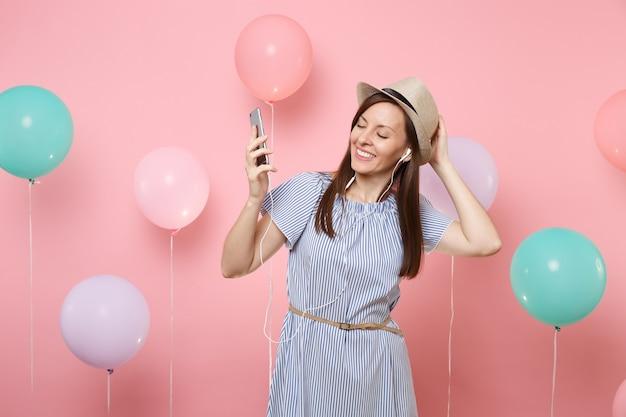 Portret van lachende jonge vrouw met gesloten ogen in stro zomerhoed blauwe jurk met mobiele telefoon en koptelefoon luisteren muziek op roze achtergrond met kleurrijke luchtballonnen. verjaardag vakantie feest.