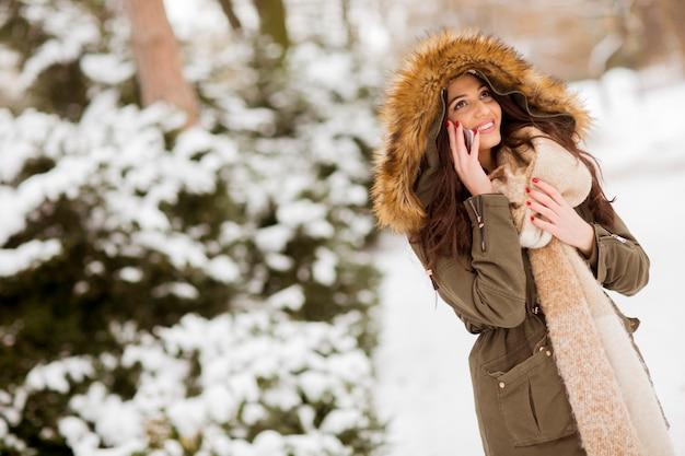 Portret van lachende jonge vrouw met mobiele telefoon in de winter buiten