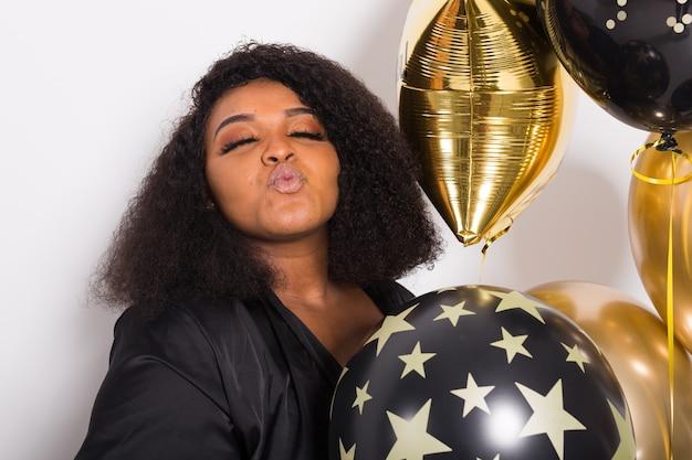 Portret van lachende jonge vrouw op zoek stijlvolle bedrijf ballonnen.
