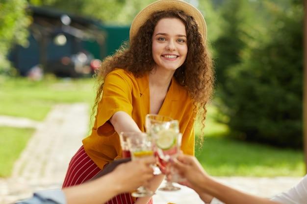 Portret van lachende jonge vrouw roosteren met vrienden terwijl u geniet van diner op terras in de zomer