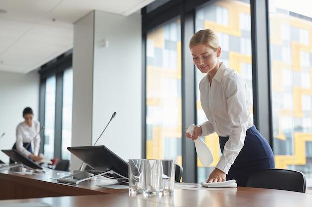 Portret van lachende jonge vrouw schoonmaaktafel met ontsmettingsspray in vergaderruimte tijdens de voorbereiding van een bedrijfsevenement in kantoor,