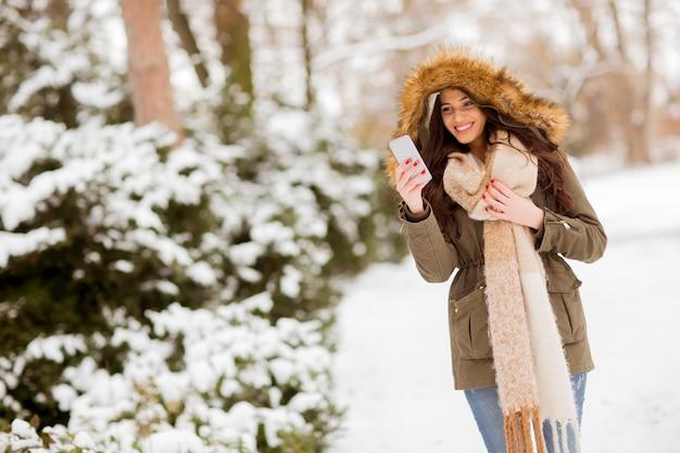 Portret van lachende jonge vrouw selfie met mobiele telefoon te nemen in de winter buiten